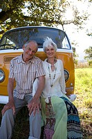 Senior couple sitting in front of camper van, smiling, portrait