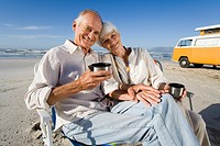Senior couple on beach by camper van drinking from insulated flask, smiling, portrait