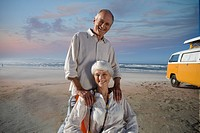 Senior couple on beach by camper van, man's hands on woman's shoulders, smiling, portrait