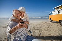 Senior woman embracing man in chair on beach by camper van, smiling, portrait