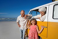 Senior couple on beach, woman in camper van holding hand of granddaughter 7-9, smiling, portrait