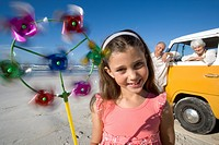 Girl 7-9 with pinwheel on beach, grandparents and camper van in background, smiling, portrait