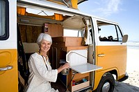 Senior woman making tea in camper van on beach, smiling, portrait, close-up