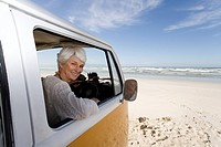 Senior woman looking out of window of camper van on beach, smiling, portrait