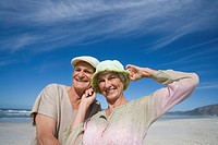 Senior couple in hats on beach, smiling, portrait, low angle view