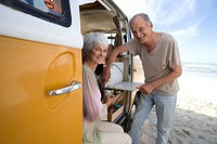Senior couple making tea in camper van on beach, smiling, portrait, side view
