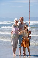 Grandparents and granddaughter 7-9 with fishing rod on beach, smiling, portrait