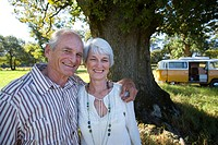 Senior couple arm in arm in field, camper van in background, smiling, portrait