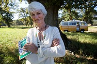 Senior woman with book in field, camper van in background, smiling, portrait
