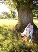 Senior couple reclining against tree in field