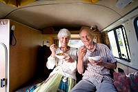 Senior couple eating breakfast in back of camper van, smiling, portrait