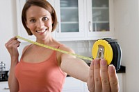 Young woman with tape measure, smiling, portrait, close-up of hand