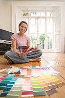 Young woman sitting with legs crossed on floor with colour swatches, smiling, portrait
