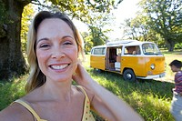 Young woman in field by camper van, smiling, portrait, close-up