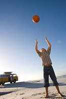 Boy 6-8 on beach throwing ball up, camper van in background, low angle view