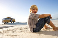 Boy 6-8 sitting on beach, camper van in background, smiling, portrait, low angle view