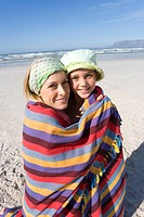 Mother and daughter 5-7 wrapped in blanket on beach, smiling, portrait, close-up