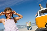 Girl 5-7 in sunglasses by family and camper van on beach, smiling, low angle view