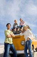 Family of four, parents by son and daughter 5-9 on roof of camper van, smiling, portrait, low angle view
