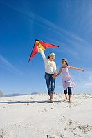 Mother and daughter 5-7 with kite on beach, smiling, low angle view