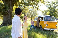 Family of four by camper van in field, woman leading man by hand, smiling, side view