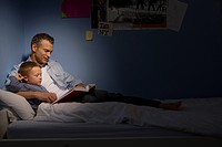 Father reading to son 4-6 in bed, side view spot lit