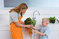 Boy 2-4 giving mother in apron bunch of carrots, smiling, side view