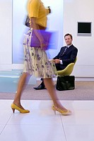 Businessman watching businesswoman walking in foyer, low section blurred motion