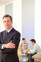 Businessman with arms crossed in office by colleagues having meeting, portrait, close-up