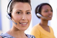 Woman in headset by colleague, smiling, portrait, close-up