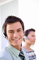 Businessman in headset by colleague, smiling, portrait, close-up