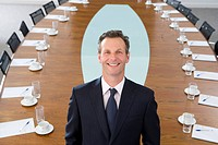 Businessman standing at head of conference table, smiling, portrait, elevated view