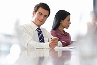 Businessman and woman at board table in meeting, portrait of man differential focus