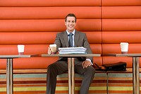 Businessman in cafe with disposable coffee cup, paperwork on table, smiling, portrait, low angle view