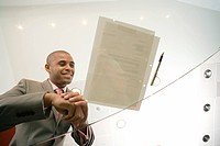 Businessman by pen and paperwork on glass table, smiling, low angle view through glass