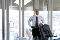 Mature businessman by desk in office, resting arm on chair, hand on hip, portrait