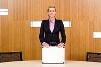 Businesswoman standing at conference table with hands on briefcase, portrait