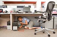 Businesswoman fixing computer under desk in office