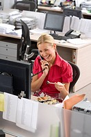 Businesswoman eating at desk in office, using telephone, smiling, elevated view
