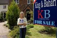 Young woman with magazine outside house with 'for sale' sign, smiling, portrait (thumbnail)