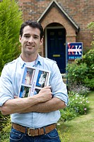 Young man with magazine outside house with 'for sale' sign, smiling, portrait