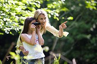 Mother pointing by daughter 7-9 using binoculars in forest