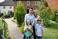 Family of four outside house, smiling, portrait (thumbnail)