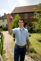 Man holding up key outside house, portrait