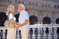 Senior couple hand in hand on bridge, smiling at each other, side view