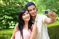 Young couple taking photograph of themselves, close-up