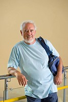 Senior man with gym bag over shoulder, leaning on railing, smiling, portrait