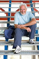 Senior man with gym bag on stairs, smiling, portrait