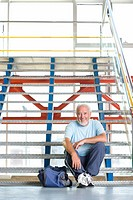 Senior man with bag on stairs, portrait, low angle view (thumbnail)