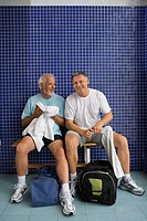 Two men in gym changing rooms, one with towel, one with water bottle, portrait
